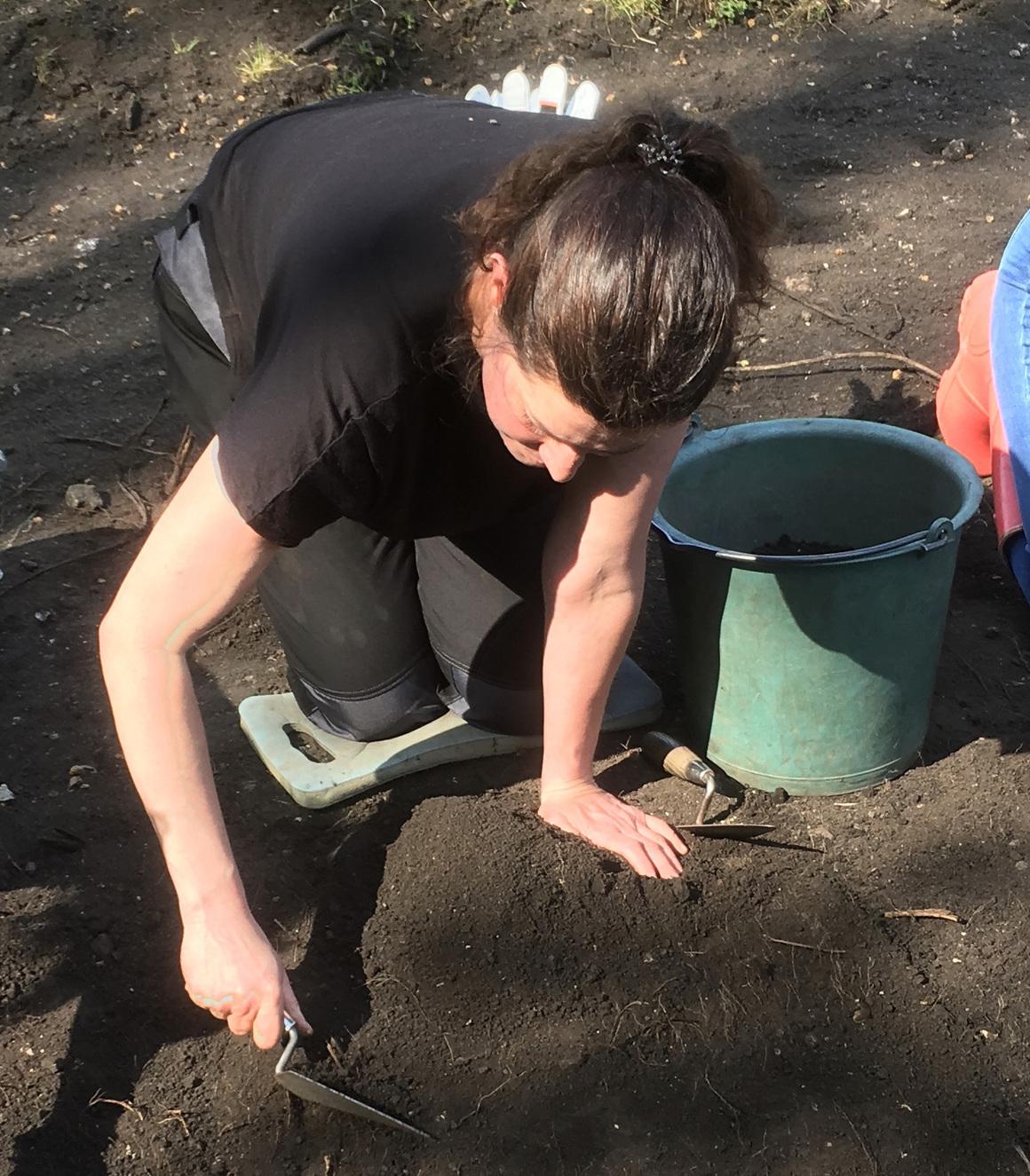 En kvinna står på knä och gräver med ett redskap