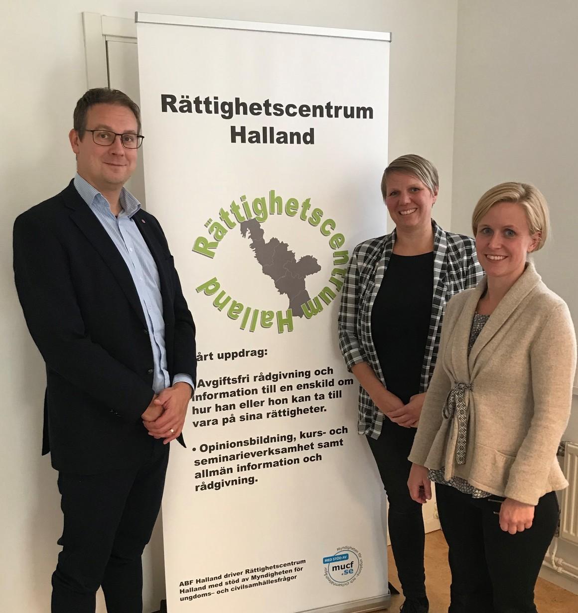 Ola Möller och Sofie och Anna från Rättighetscentrum Halland står framför en roll-up med text och logga för Rättighetscentrum Halland