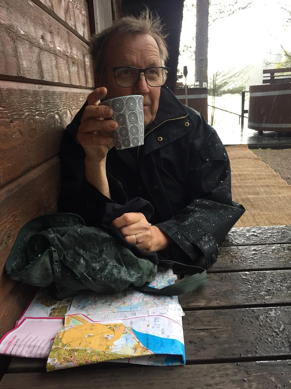 Man med hittautkarta fikar i skydd av regnet