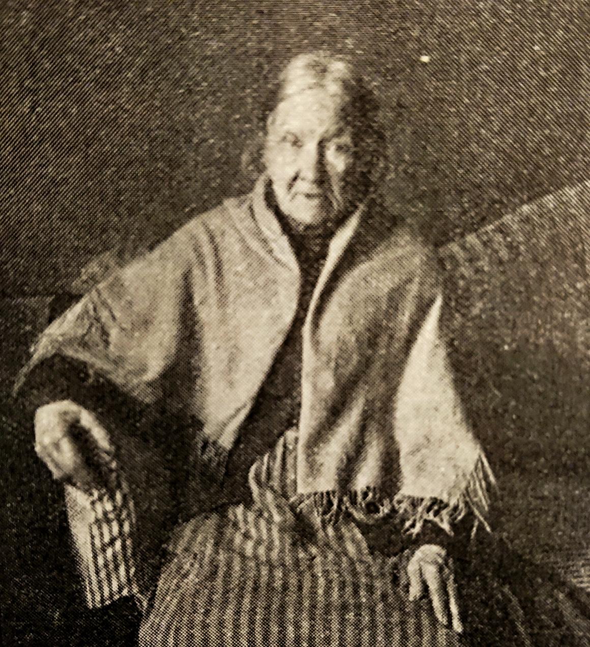 Gammalt svartvitt foto visar en äldre kvinna med sjal över axlarna