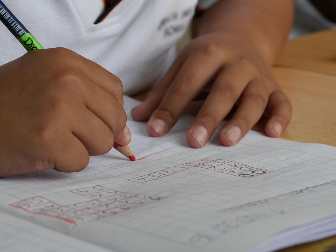 En bild med två barnhänder som håller en hända som skriver i ett block