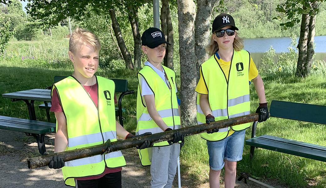 Tre unga innebandylirare med ett järnrör som de hittat i naturen.