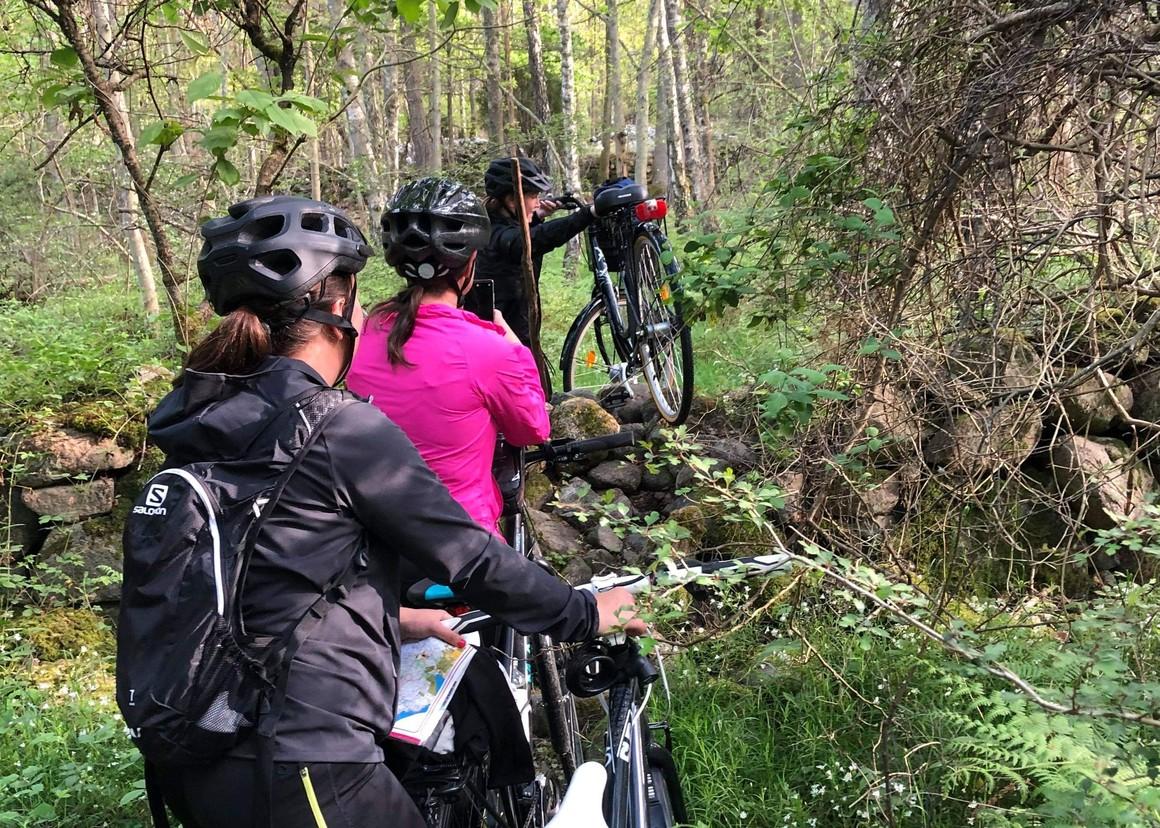 Kvinnor bär cyklar över stenmur