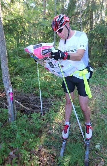Man på rullskidor med hjälm och stavar läser hittautkarta i skog vid checkpoint