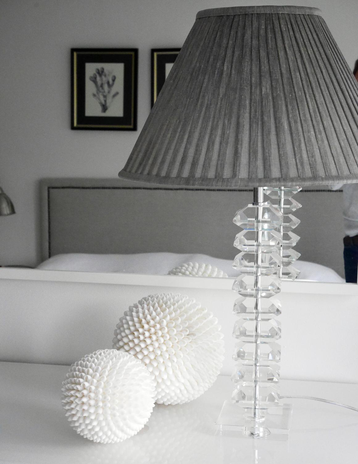 Lampfot i glas med grå plisserad skärm.