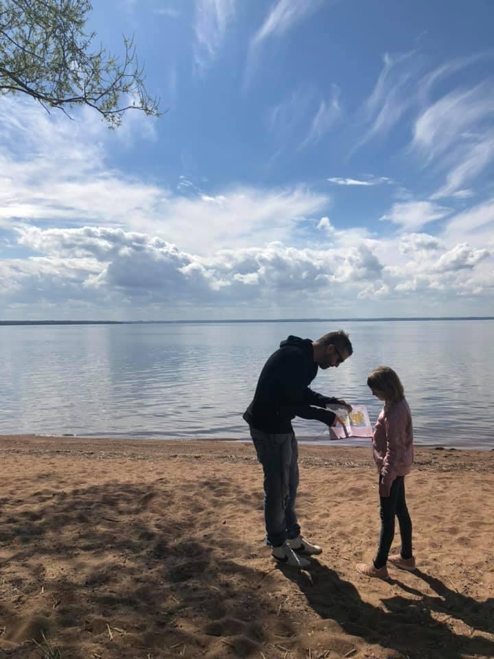 Pappa och dotter med hittautkarta på strand vid sjö