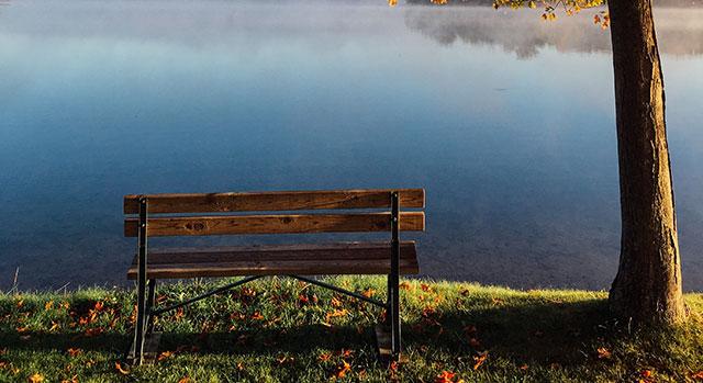 Höstbild på en bänk vid en sjö
