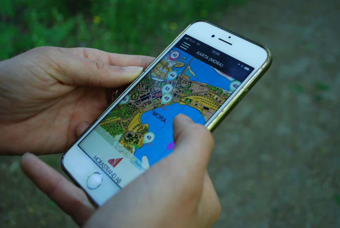 Två händer håller i mobil där hittauts app visas
