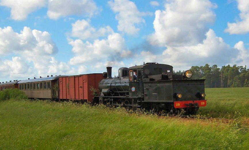 Gammalt tåg rullar genom svensk natur